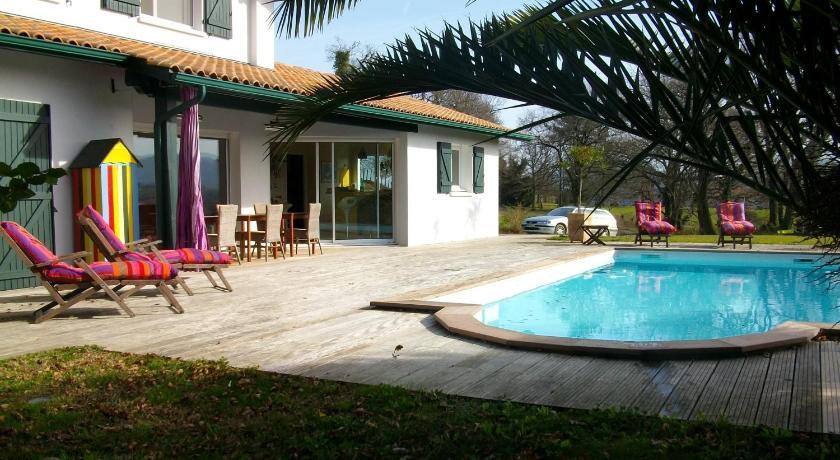 室外游泳池、带顶棚的露台和一个包含烧烤设施的夏季厨房.