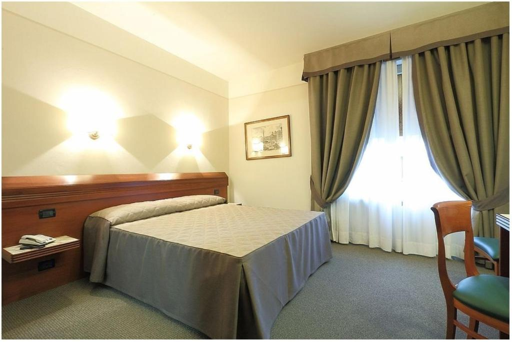 A bed or beds in a room at Hotel Arcadia