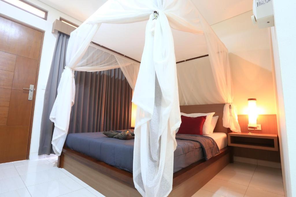 En eller flere senge i et værelse på Gembala Homestay