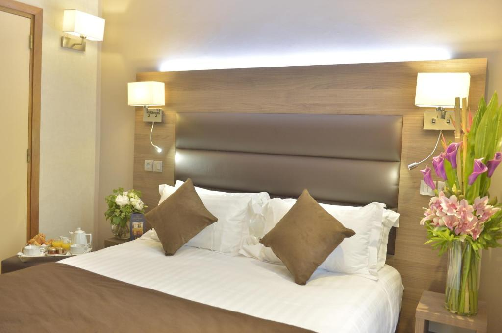 A bed or beds in a room at Hôtel Renoir Montparnasse