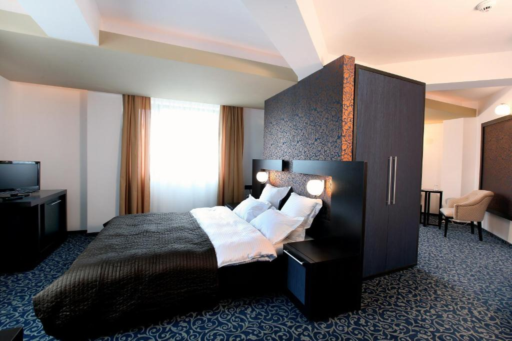 A bed or beds in a room at Ambiance Hotel