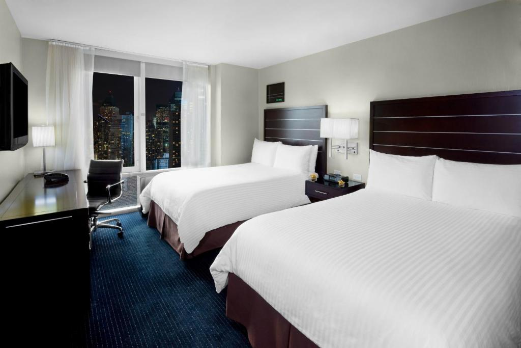 A bed or beds in a room at Hilton New York Fashion District