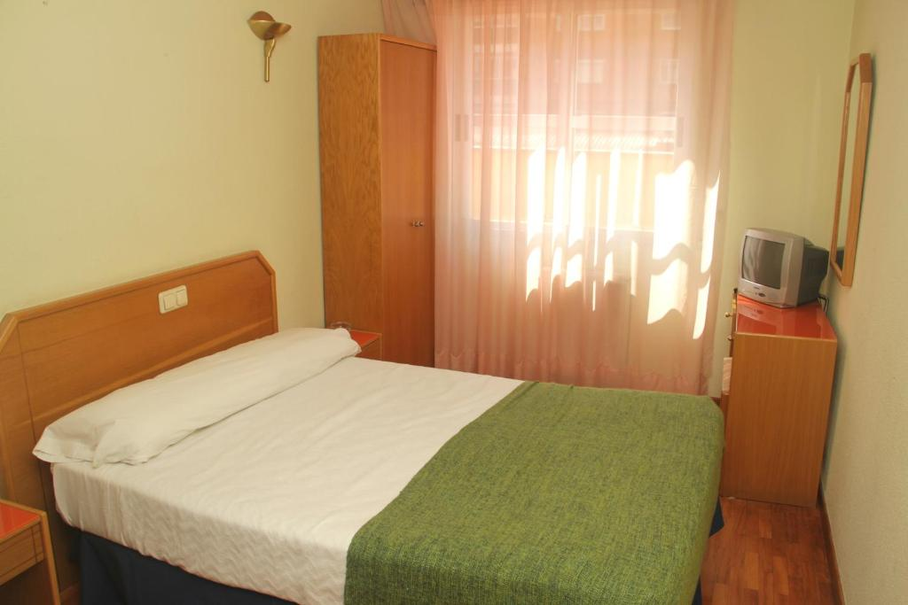 A bed or beds in a room at Hostal Arlanzón
