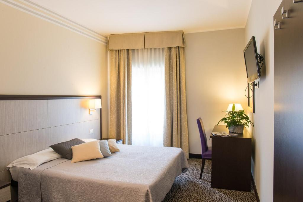 Een bed of bedden in een kamer bij Hotel Alpi Resort