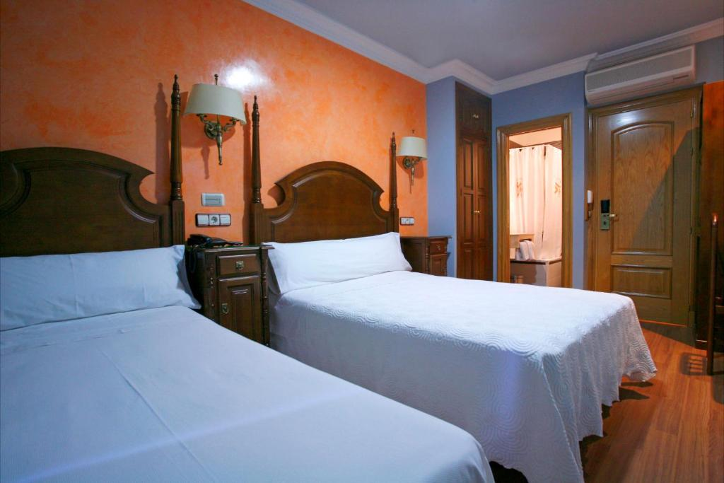 A bed or beds in a room at Hostal Victoria II