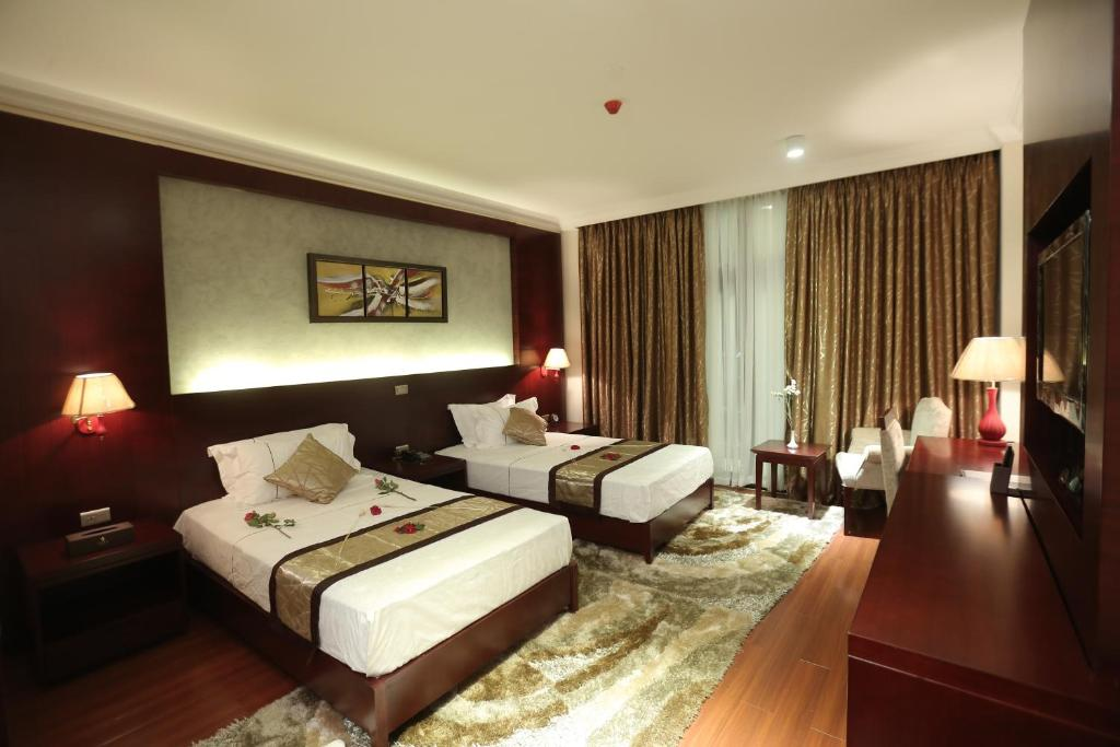 A bed or beds in a room at Sidra International Hotel