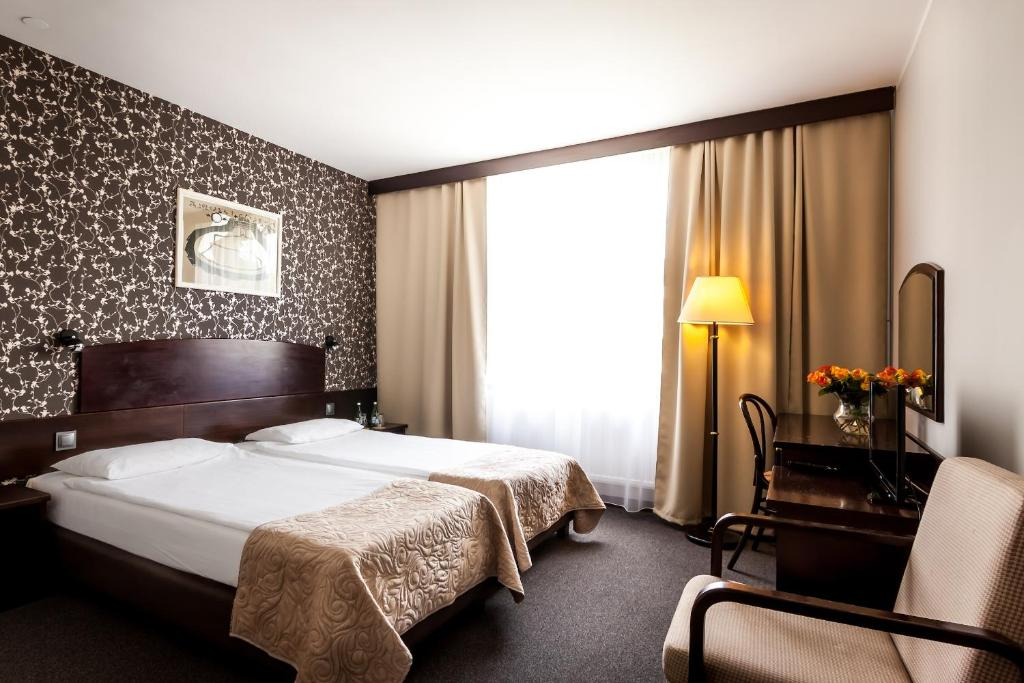 A bed or beds in a room at Go Cracow Resort