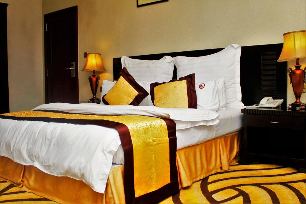 A bed or beds in a room at Galaxy Hotel