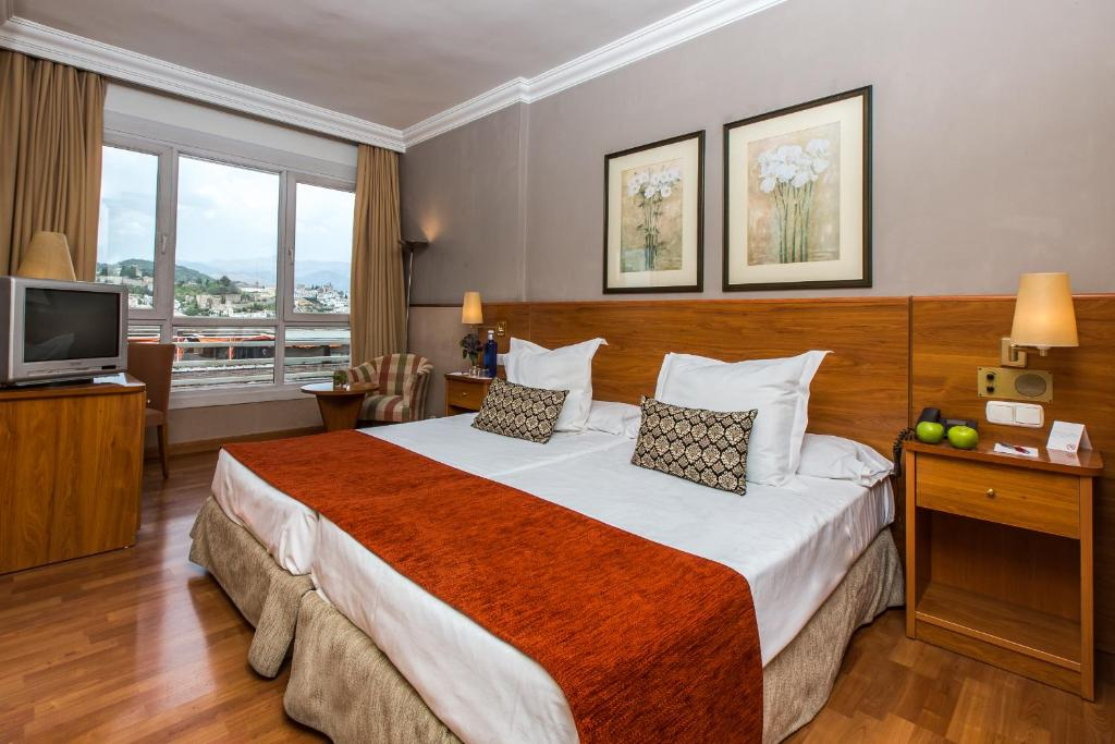 A bed or beds in a room at Leonardo Hotel Granada
