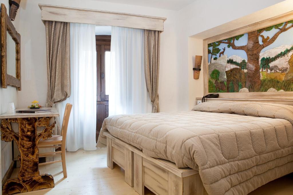 A bed or beds in a room at Garnì La Rua nel Bosco