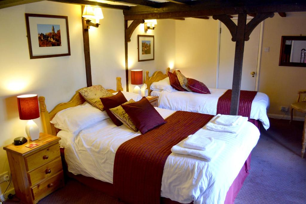 A bed or beds in a room at The Bull's Head Inn