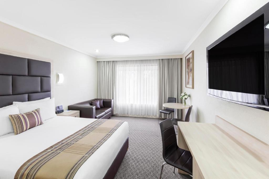 A television and/or entertainment center at Garden City Hotel, Best Western Signature Collection