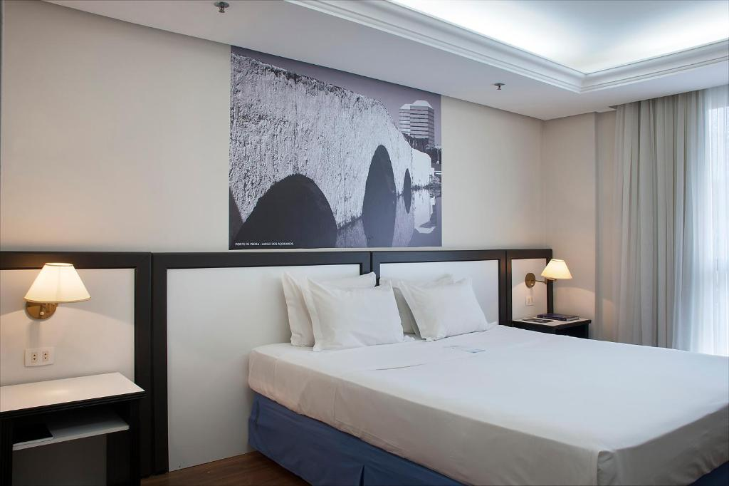 A bed or beds in a room at Master Grande Hotel