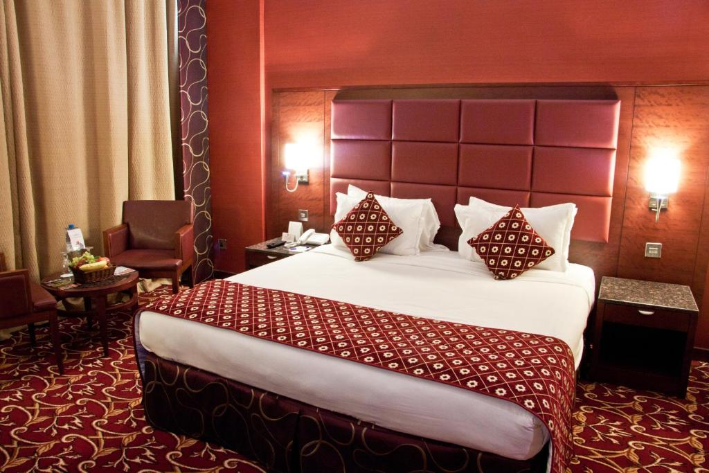 A bed or beds in a room at Ramee Rose Hotel