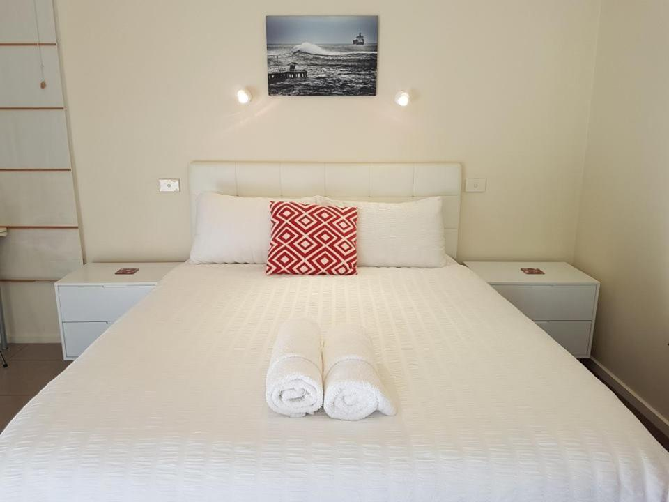 A bed or beds in a room at Springtide Studio Apartments