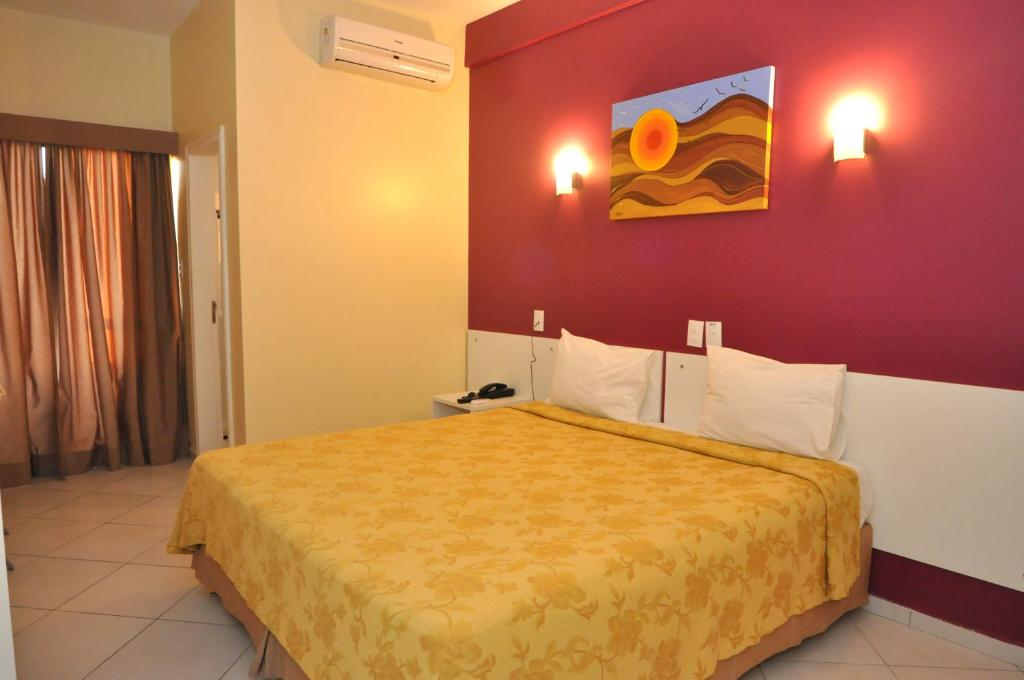 A bed or beds in a room at Sandrin Praia Hotel