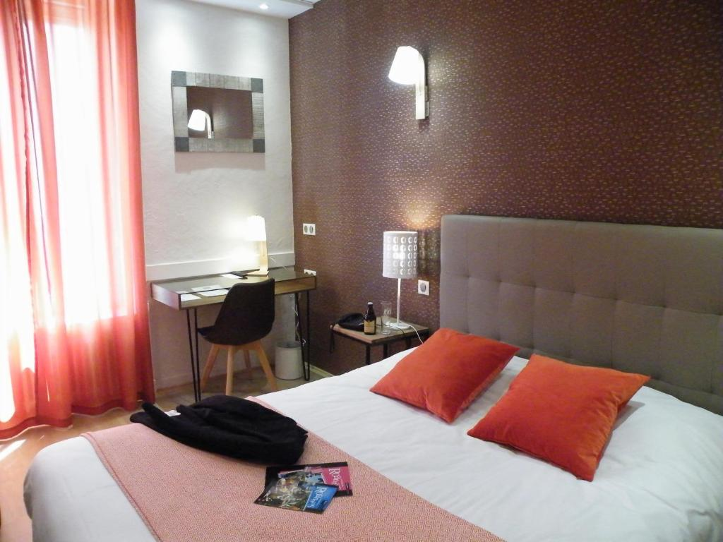 A bed or beds in a room at Brit Hotel Roanne - Le Grand Hôtel