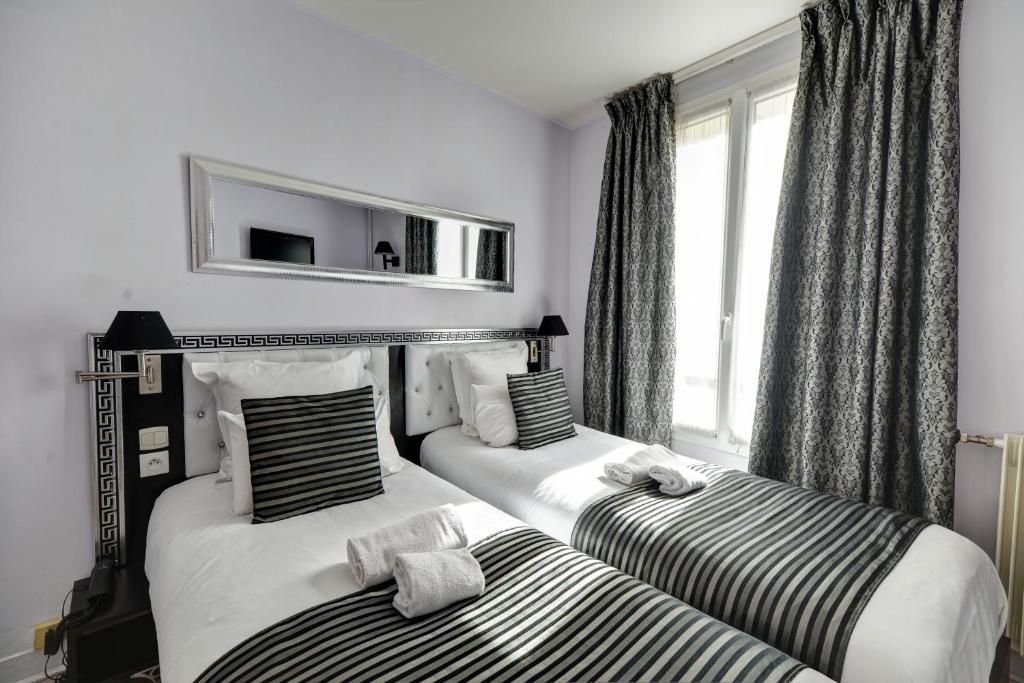 A bed or beds in a room at Pavillon de Montmartre