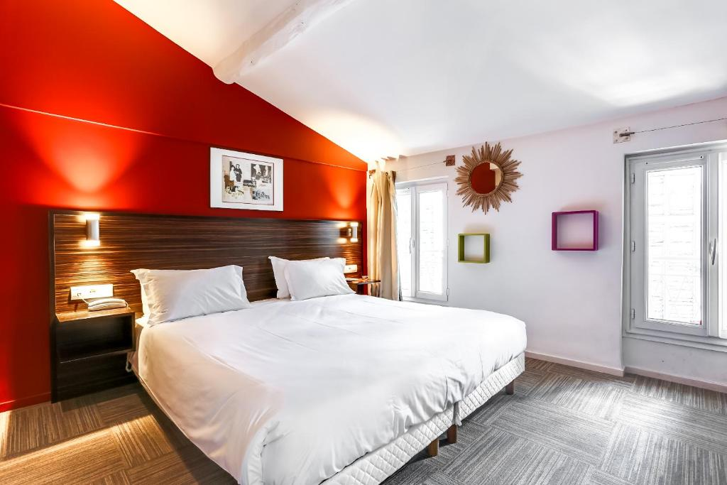 A bed or beds in a room at Hotel Le Mistral