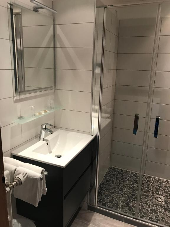 A bathroom at Hotel Restaurant Aux Trois Roses