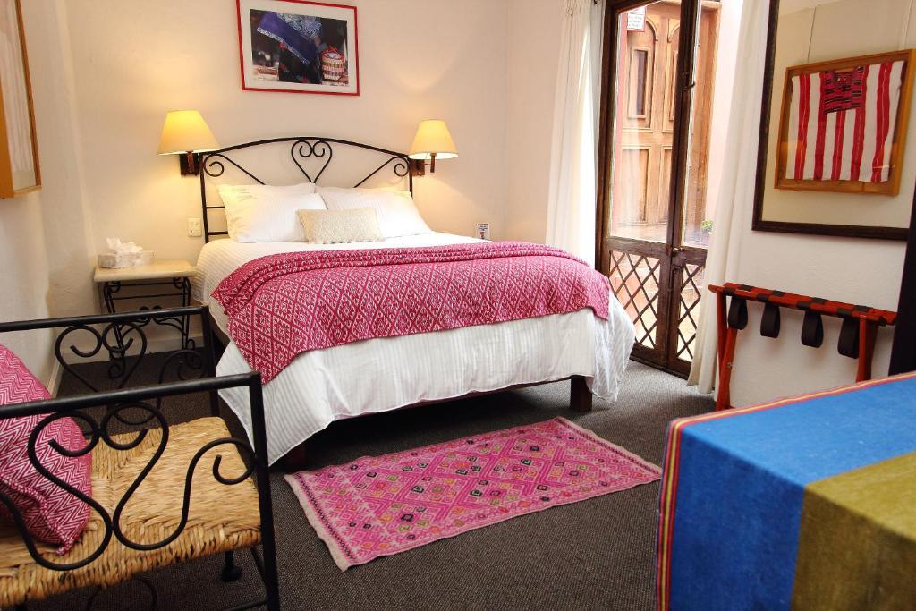 A bed or beds in a room at Misión Grand San Cristóbal de las Casas