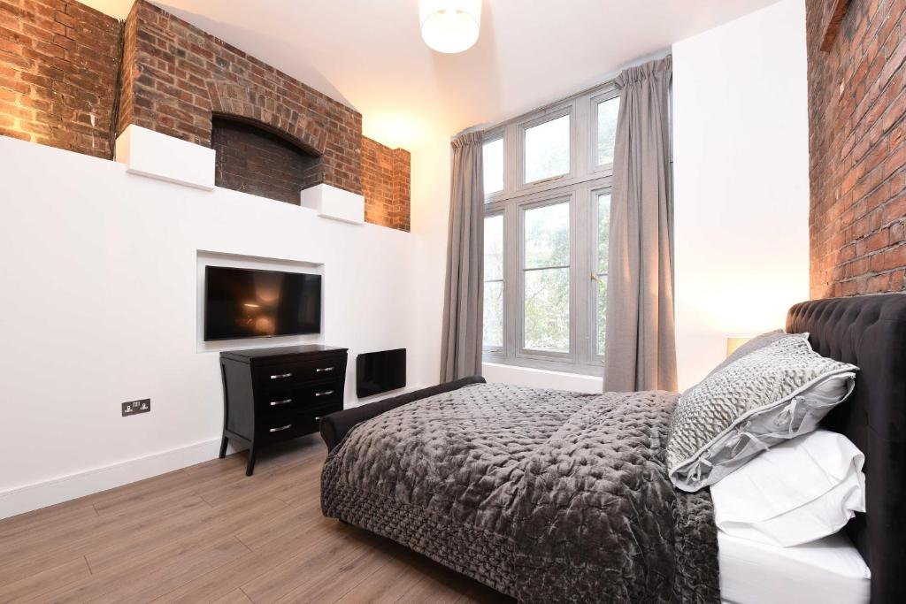 A television and/or entertainment centre at Spacious & Modern 2 Bed Apartment at Knightsbridge London