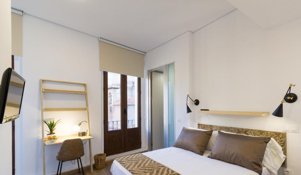 A bed or beds in a room at The Bridge Huertas