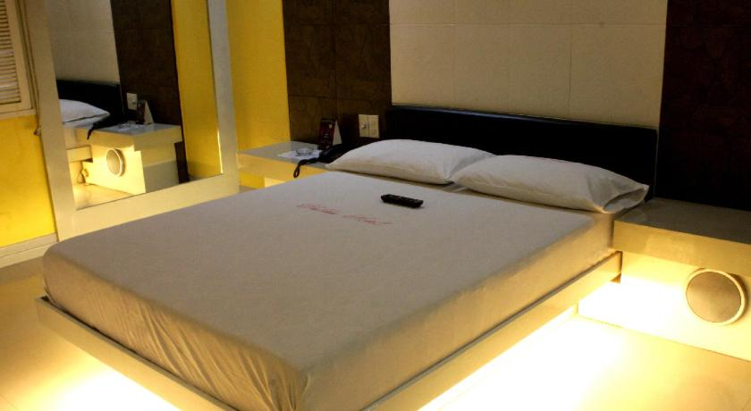 A bed or beds in a room at Dahlia Hotel