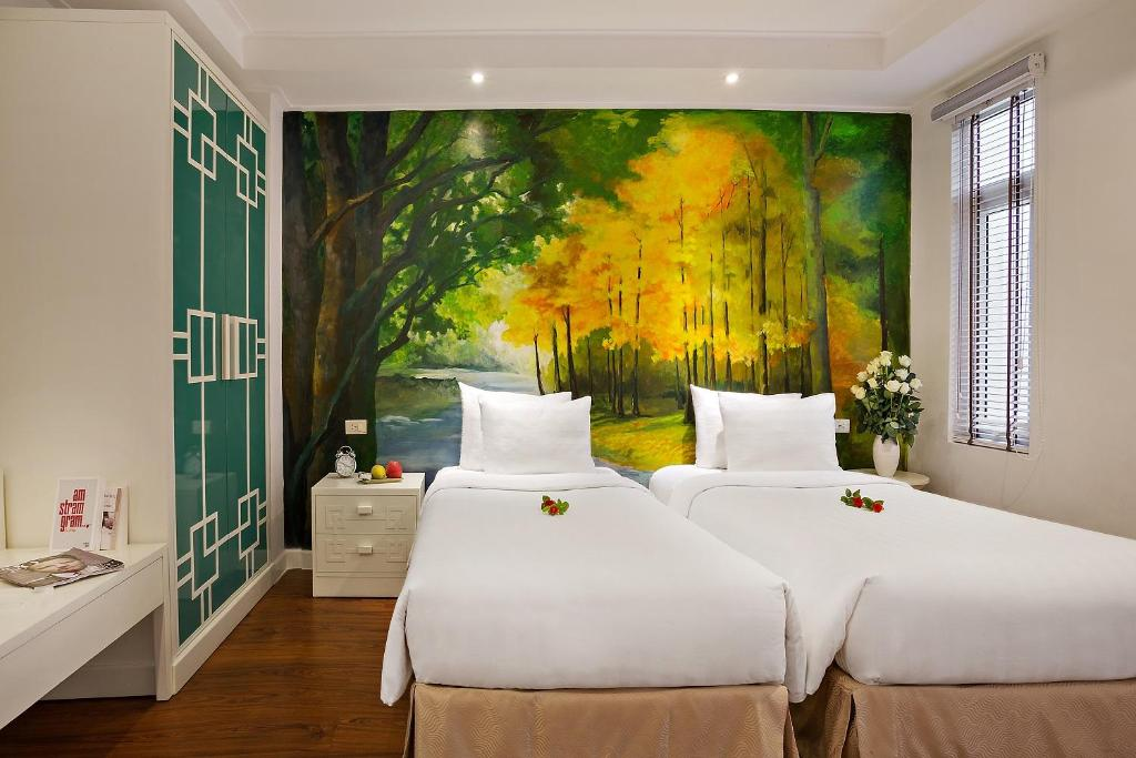 A bed or beds in a room at Hanoi La Selva Hotel