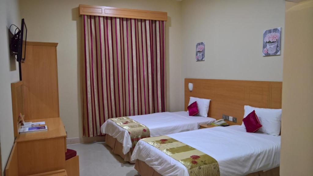 سرير أو أسرّة في غرفة في السلام إن للأجنحة الفندقية