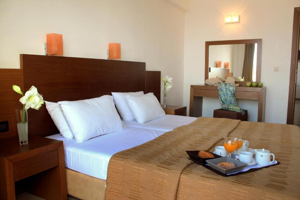 A bed or beds in a room at Rodian Gallery Hotel Apartments