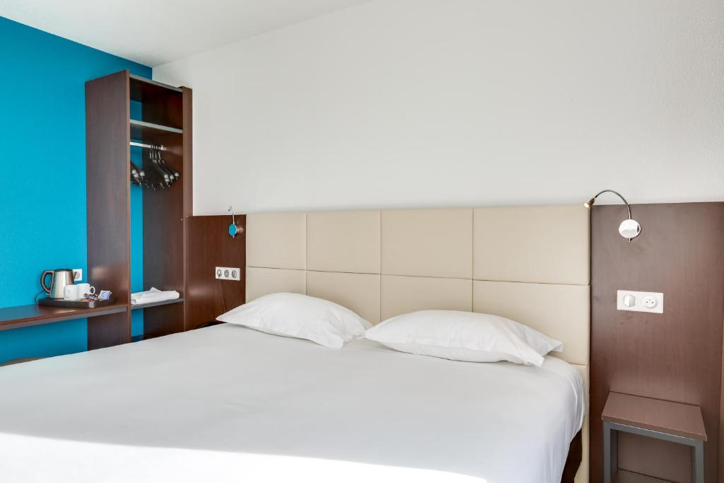 A bed or beds in a room at Inspiration by balladins Caen Mémorial