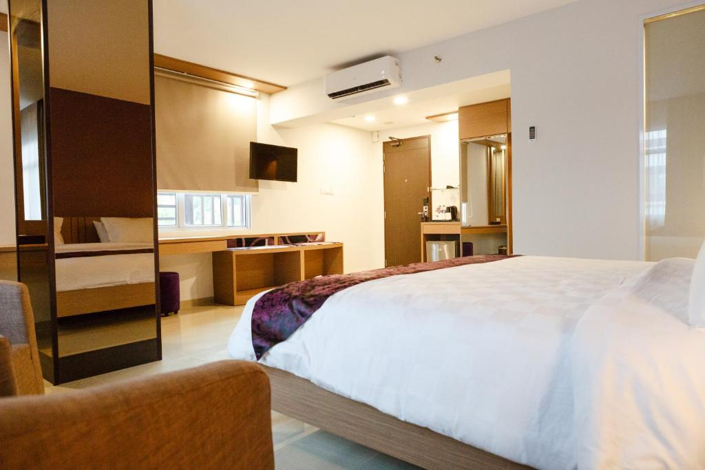 A bed or beds in a room at The Evitel Hotel Batam