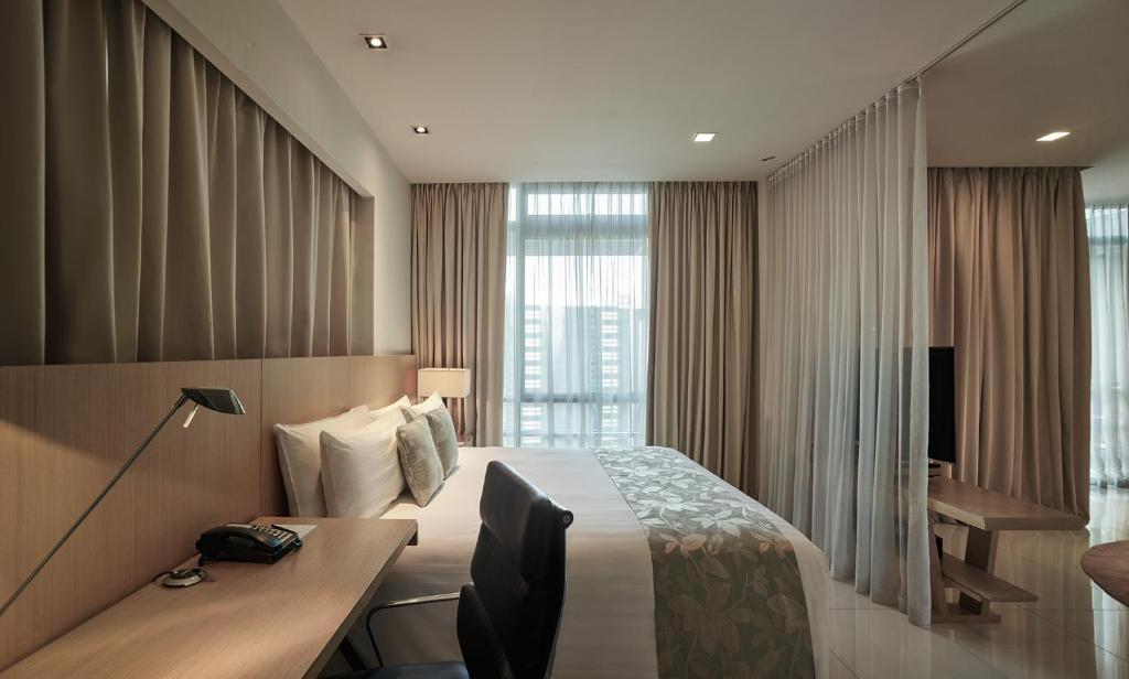 A bed or beds in a room at PARKROYAL Serviced Suites Kuala Lumpur