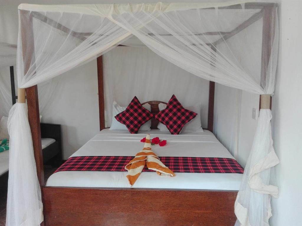 A bed or beds in a room at Kihori Bungalows