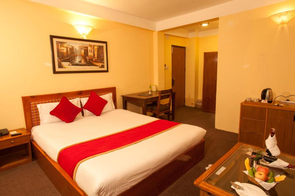 A bed or beds in a room at Royal Astoria Hotel