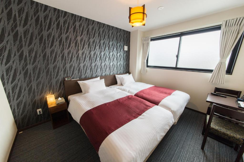 A bed or beds in a room at JAPANING HOTEL Kyoto Hachijoguchi