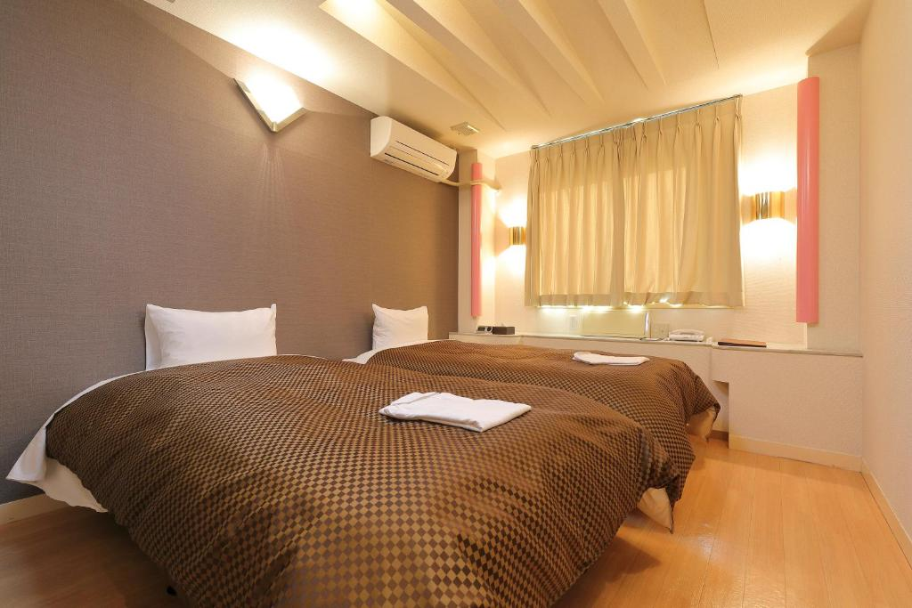 A bed or beds in a room at Reco Hotel Mikuni