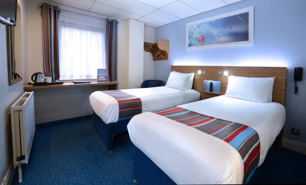 A bed or beds in a room at Travelodge Belfast