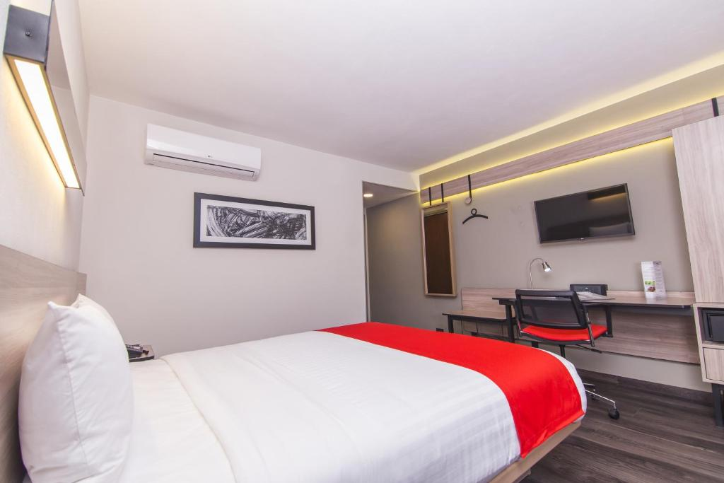 A bed or beds in a room at City Express Plus Bogota Aeropuerto