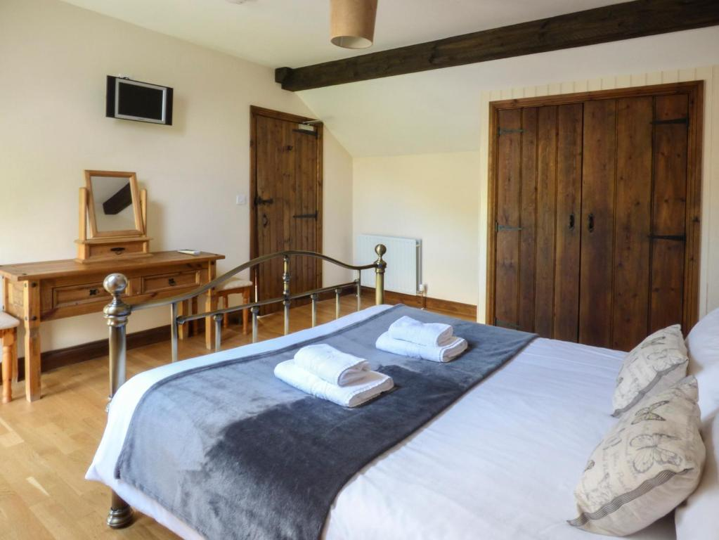 A bed or beds in a room at Oak Tree Cottage, Penrith