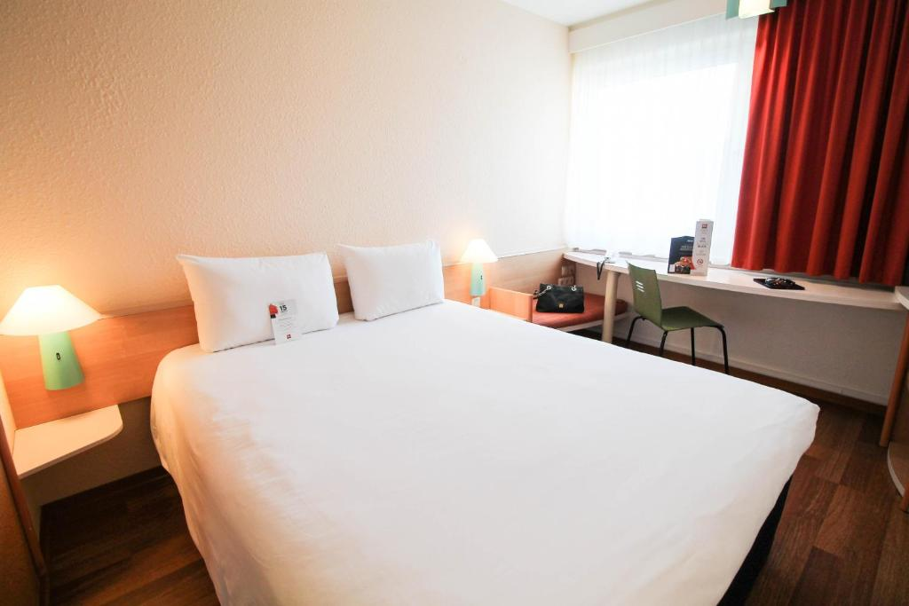 A bed or beds in a room at ibis Hotel Düsseldorf Hauptbahnhof