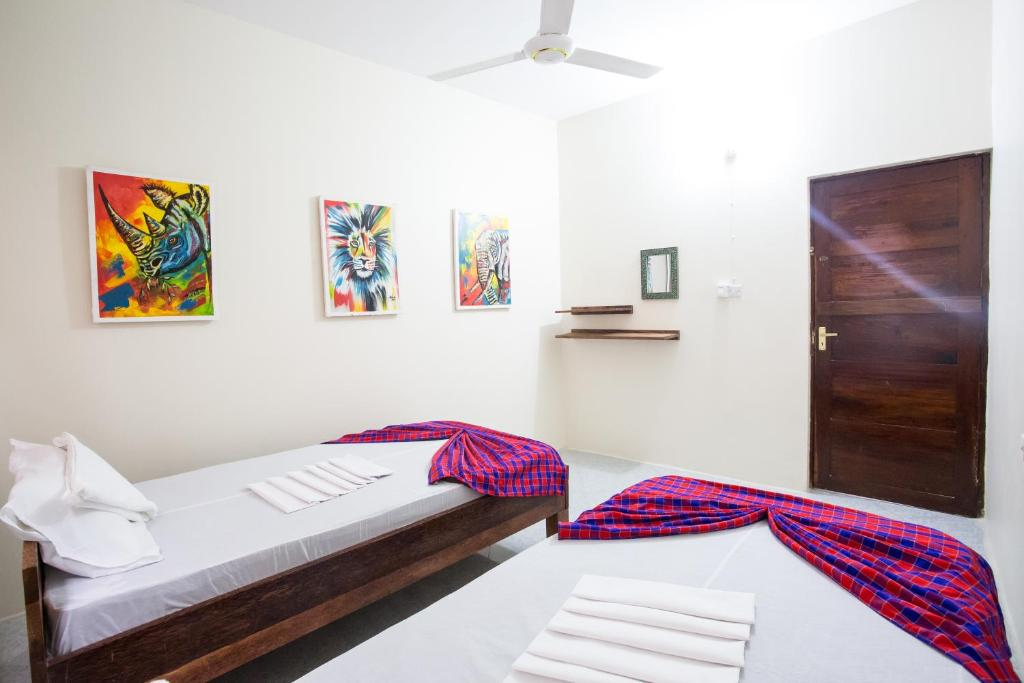 A bed or beds in a room at Ten to Ten Stone Town Zanzibar