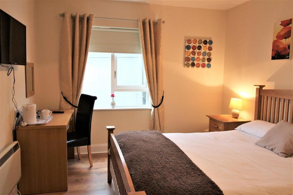 A bed or beds in a room at The Connaught Inn