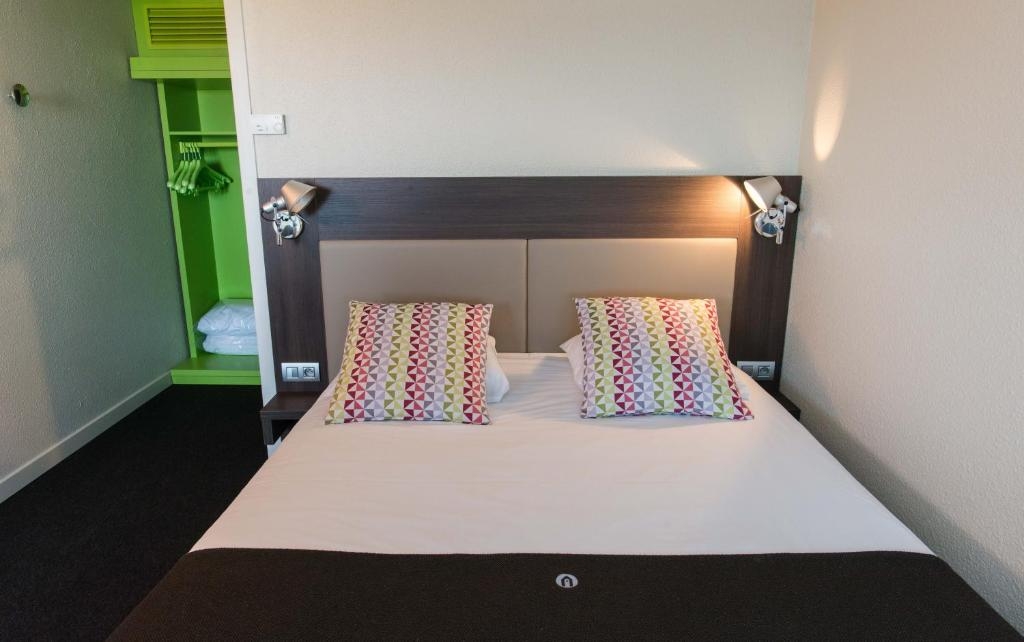A bed or beds in a room at Campanile Deauville Saint-Arnoult