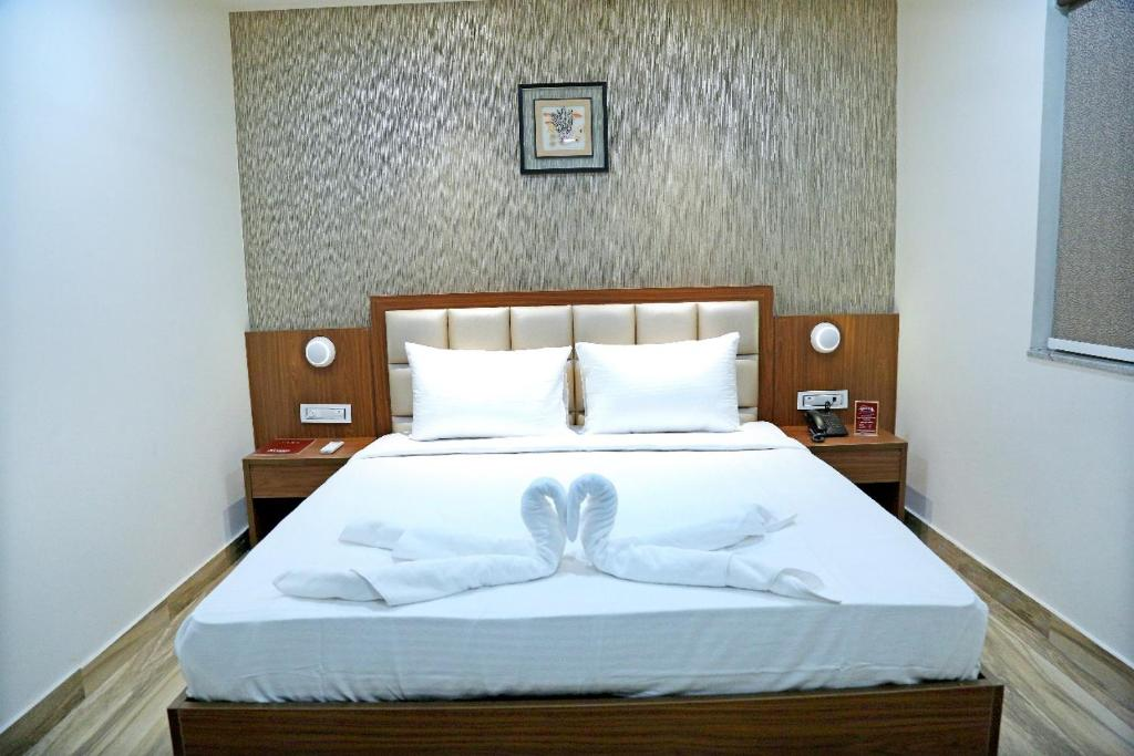 A bed or beds in a room at Hotel Shubham Celebrations