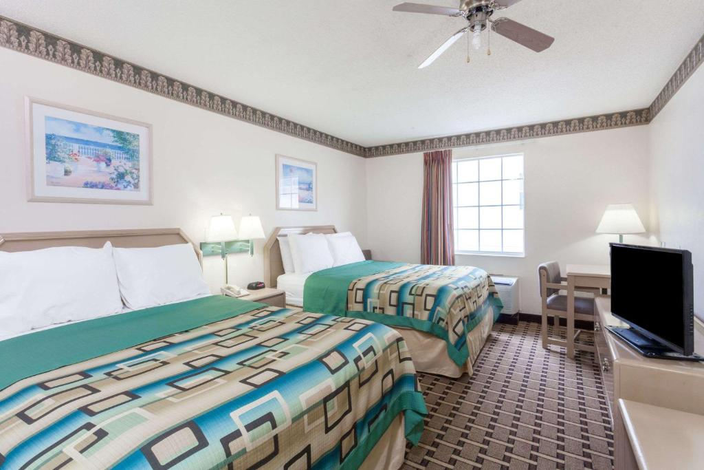 A bed or beds in a room at Days Inn & Suites by Wyndham Huntsville