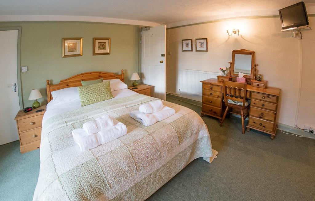 A bed or beds in a room at Warren House B&B