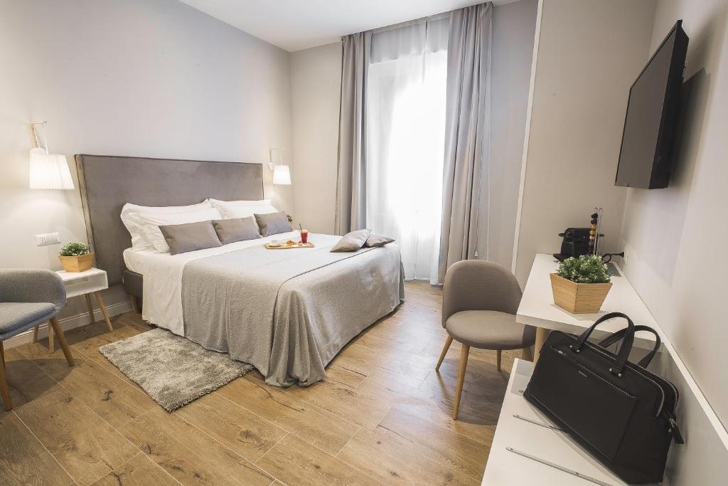 A bed or beds in a room at Colonna Luxury Suites