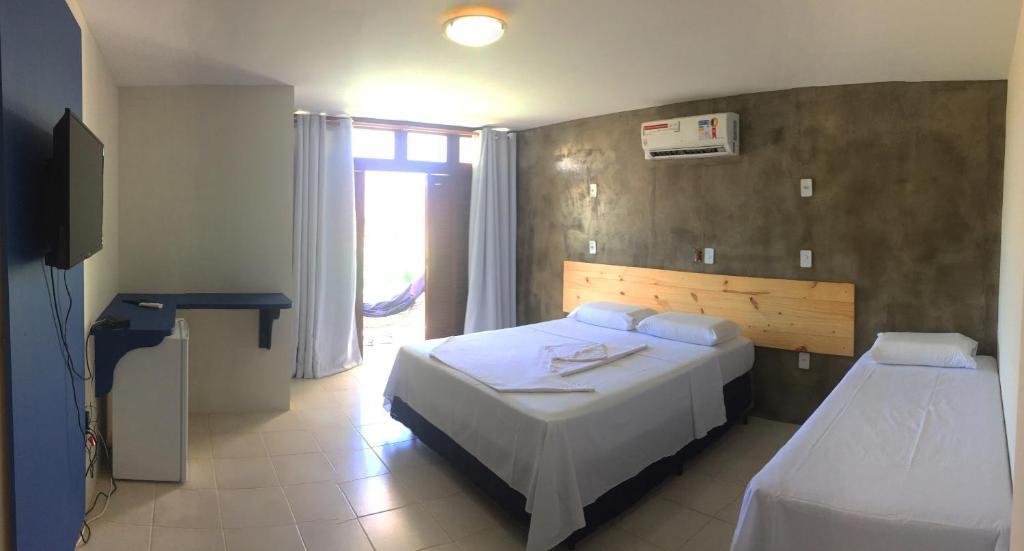 A bed or beds in a room at Pousada Kalani